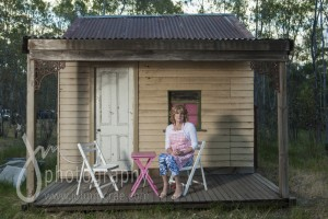 Denise sitting on the verandah of her small home