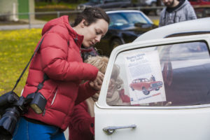 Elle and Denise adhering a flyer to the car window